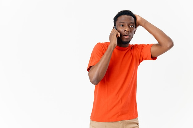 Jeune homme parlant sur un téléphone portable dans un t-shirt orange