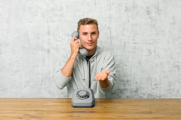 Jeune homme parlant sur un téléphone vintage tenant quelque chose avec des paumes, offrant à la caméra.