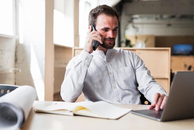 Jeune homme parle au téléphone portable tout en travaillant sur un ordinateur portable