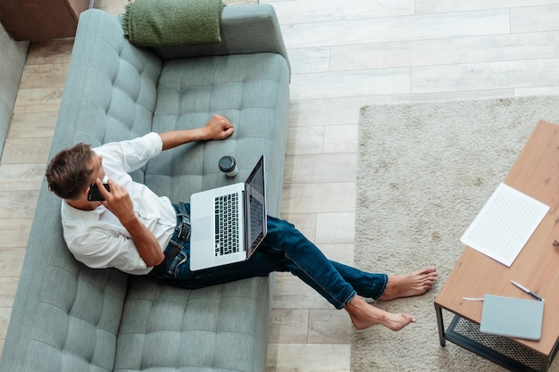 Jeune homme parle sur un smartphone, assis sur le canapé