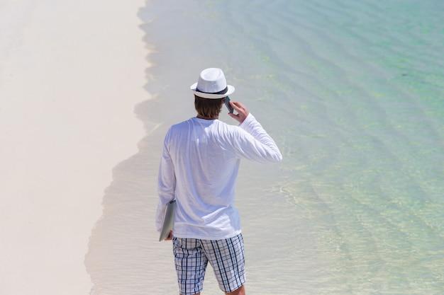 Jeune homme parle de téléphone portable sur la plage tropicale