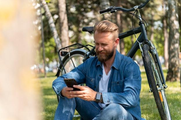 Jeune homme passant du temps à l'extérieur avec son vélo