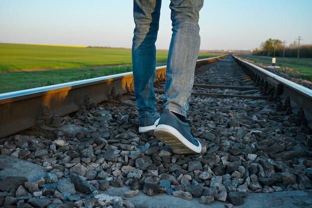 Jeune homme passant le long de la voie ferrée.