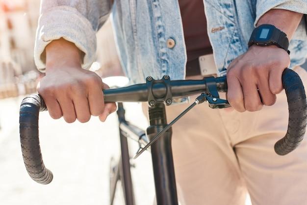 Jeune homme passe-temps marchant sur la rue de la ville avec un vélo tenant un gouvernail en gros plan
