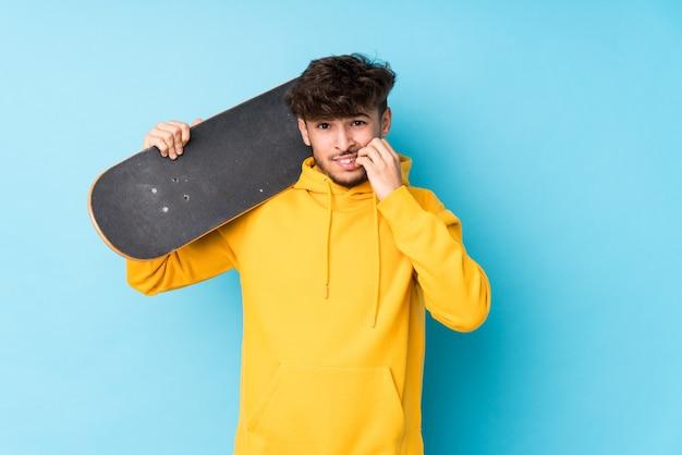 Jeune homme de patineur arabe a isolé les ongles mordants, nerveux et très anxieux.