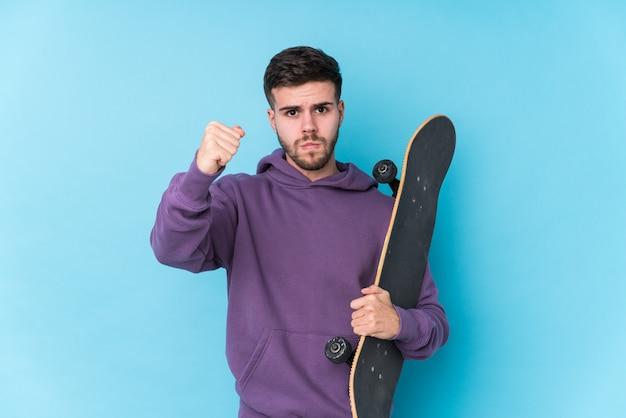 Jeune homme de patineur caucasien isolé montrant le poing avec une expression faciale agressive.