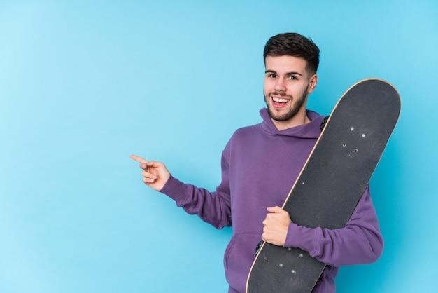 Jeune homme de patineur caucasien isolé souriant et pointant de côté, montrant quelque chose à l'espace vide.