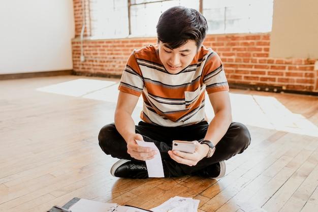 Jeune homme payant des factures en ligne via internet banking