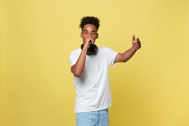 Jeune homme à la peau foncée avec une coupe de cheveux afro en t-shirt blanc, gesticulant avec les mains