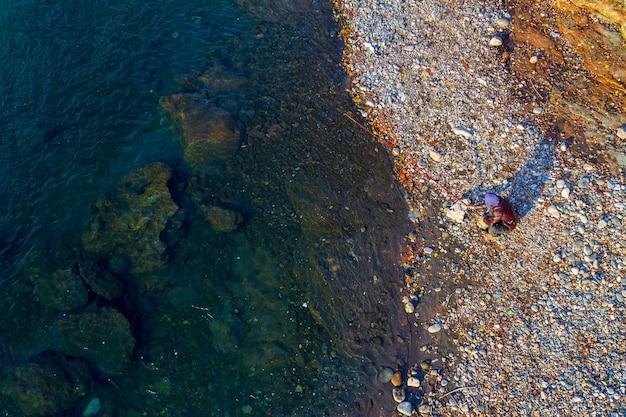Jeune homme pêchant dans la rivière un jour d'automne, vue du dessus