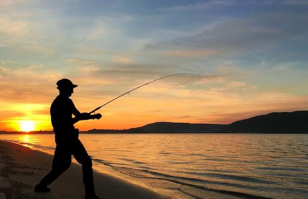 Jeune homme pêchant sur un lac au coucher du soleil