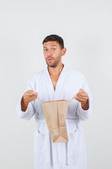 Jeune homme en peignoir blanc ouverture sac en papier et à la curieuse, vue de face.