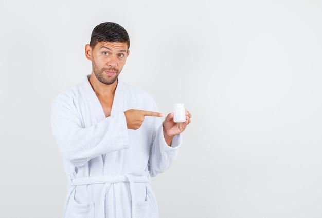 Jeune homme en peignoir blanc pointant sur le flacon de médicament en plastique, vue de face.