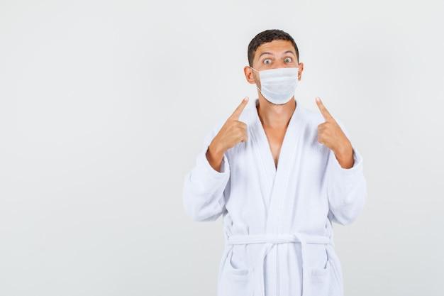 Jeune homme en peignoir blanc pointant sur le masque et regardant prudemment, vue de face.