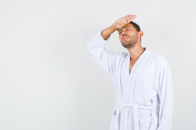 Jeune homme en peignoir blanc souffrant de fièvre et l'air fatigué, vue de face.