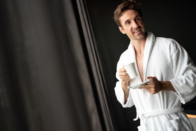 Jeune homme en peignoir buvant du café à l'hôtel, centre de spa.