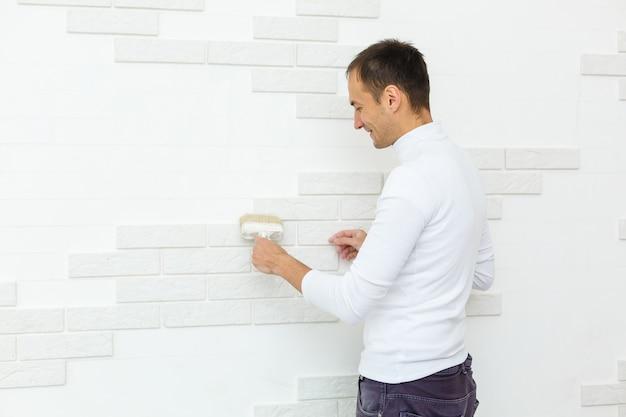 Le jeune homme peint une tuile de brique avec une brosse
