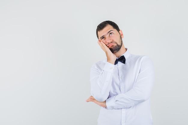 Jeune homme penchant la joue sur la paume surélevée en chemise blanche et à la pensif. vue de face.
