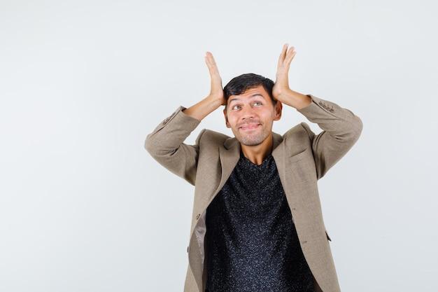 Jeune homme penché les mains levées sur sa tête en veste marron grisâtre et l'air amusé, vue de face.