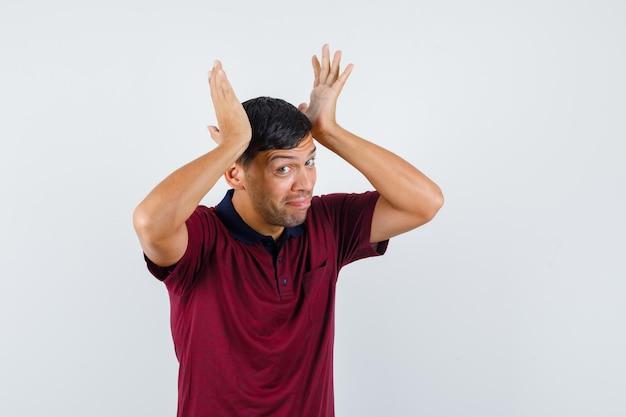 Jeune homme penché les mains levées sur la tête en t-shirt et à la confusion, vue de face.