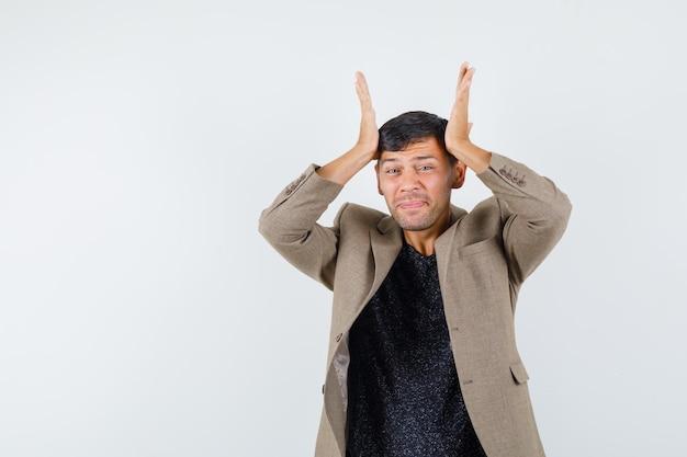 Jeune homme penché les mains levées sur la tête en veste marron grisâtre et l'air confus. vue de face.