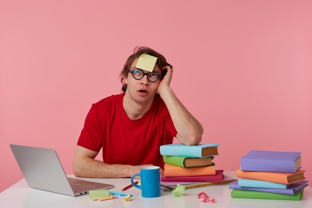 Jeune homme pencive à lunettes porte en t-shirt rouge, est assis près de la table et travaille avec un cahier et des livres, avec un autocollant sur son front, lève les yeux et pense, isolé sur fond rose.