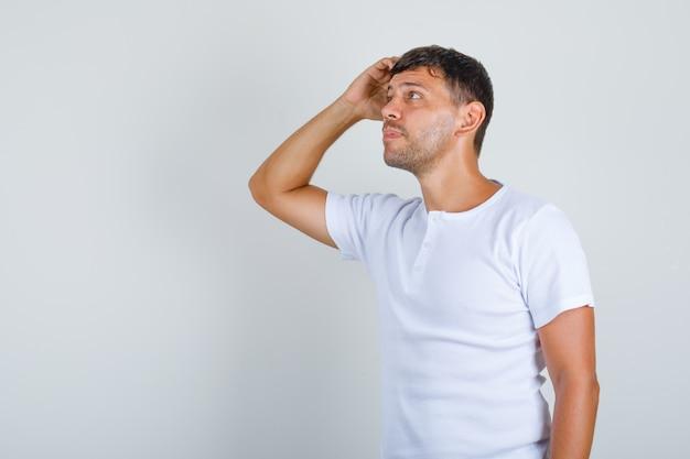 Jeune homme pensant avec la main sur la tête en t-shirt blanc, vue de face.
