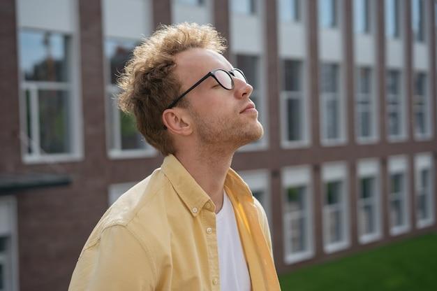 Jeune homme pensif aux yeux fermés respirant de l'air frais relaxant dans le concept de désintoxication numérique du parc