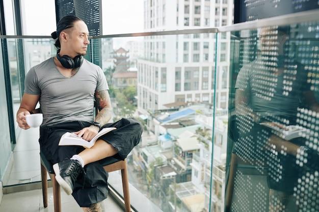 Jeune homme pensif avec un livre ouvert buvant du café et regardant la grande ville depuis le balcon de son appartement