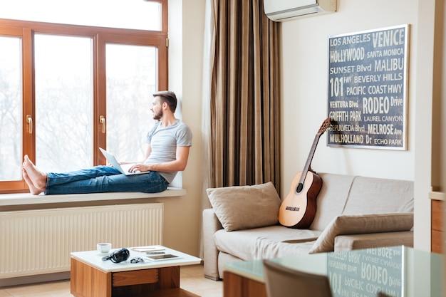 Jeune homme pensif avec ordinateur portable assis sur le rebord de la fenêtre à la maison