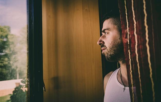 Jeune homme pensif parmi les rideaux