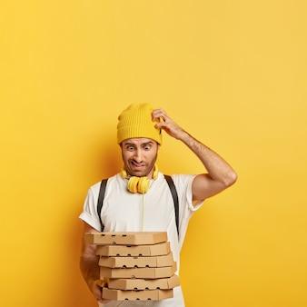 Un jeune homme perplexe se gratte la tête, regarde avec étonnement une pile de boîtes en carton avec de la pizza, n'a pas le temps de livrer tous ces colis