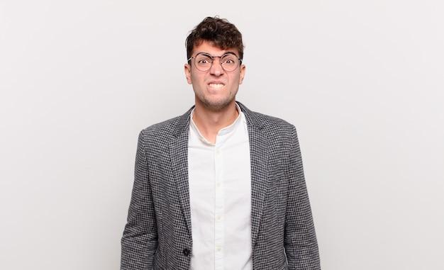 Jeune homme à la perplexité et confus, mordant la lèvre avec un geste nerveux, ne sachant pas la réponse au problème