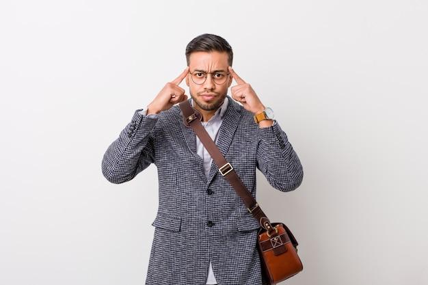 Jeune homme philippin d'affaires contre un mur blanc concentré sur une tâche, gardant les index pointant la tête.