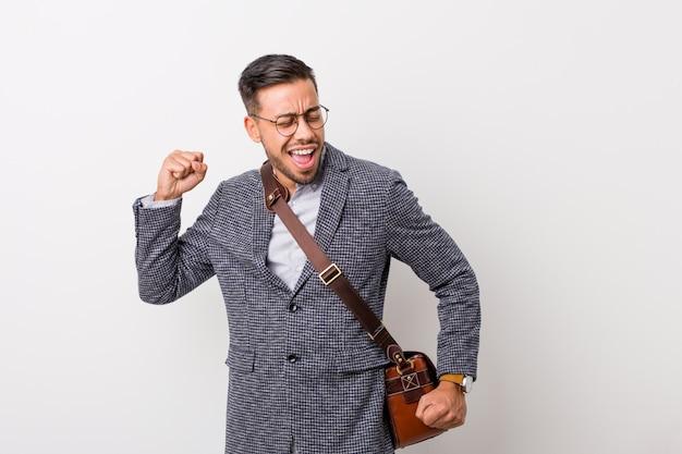 Jeune homme philippin d'affaires contre un mur blanc dansant et s'amusant.