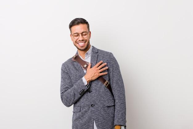Jeune homme philippin d'affaires contre un mur blanc éclate de rire en gardant la main sur la poitrine.