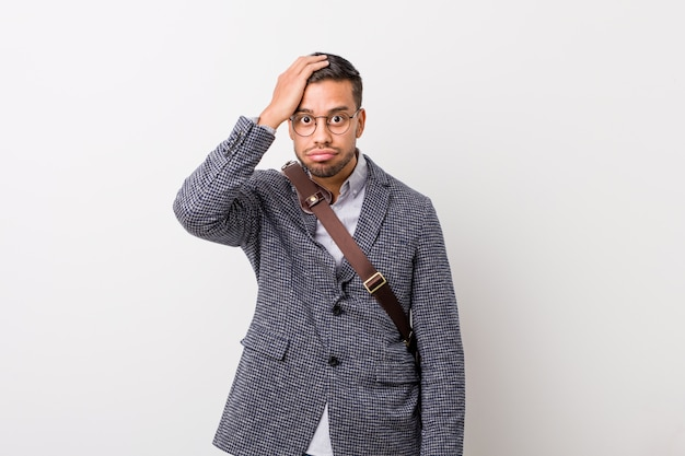 Jeune homme philippin d'affaires contre un mur blanc fatigué et très endormi en gardant la main sur la tête.