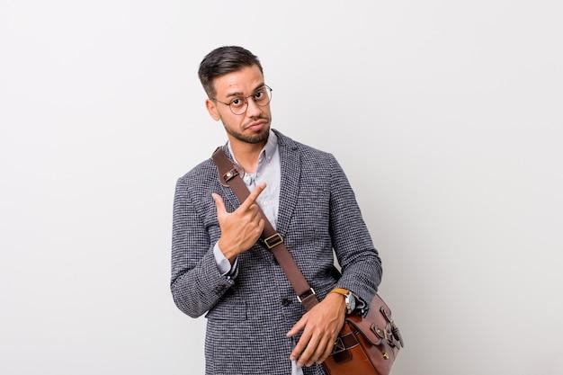 Jeune homme philippin d'affaires contre un mur blanc pointant avec le doigt vers vous comme si vous vous invitiez à vous rapprocher.