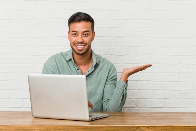 Jeune homme philippin assis travaillant avec son ordinateur portable montrant un espace de copie sur une paume