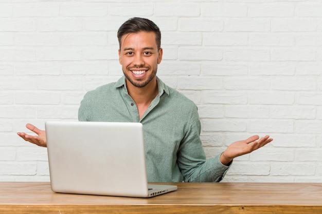 Jeune homme philippin assis travaillant avec son ordinateur portable montrant une expression bienvenue.