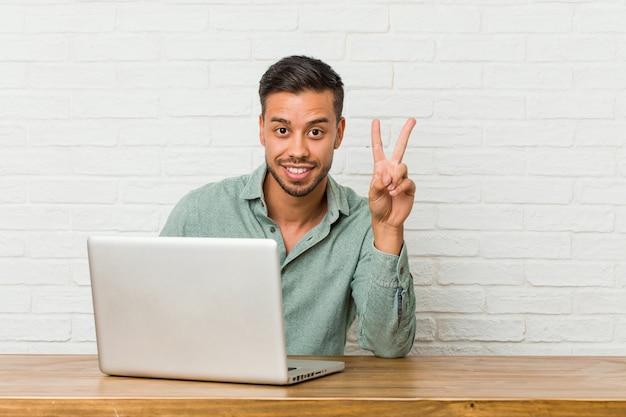 Jeune homme philippin assis travaillant avec son ordinateur portable montrant le numéro deux avec les doigts.