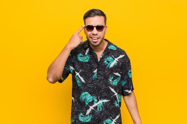 Jeune homme philippin portant des vêtements d'été montrant un geste de déception avec l'index.