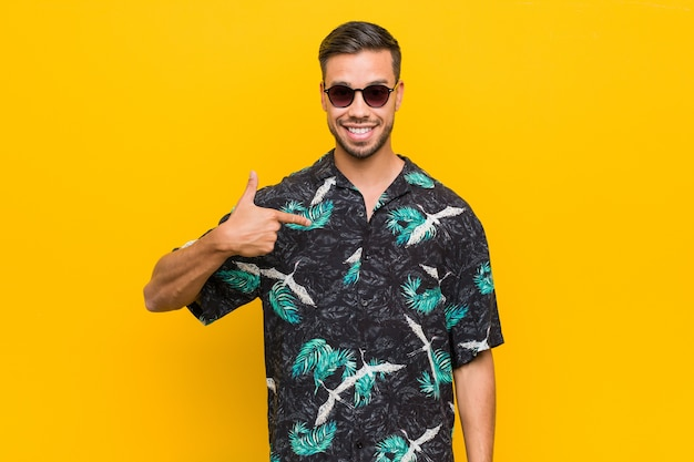 Jeune homme philippin portant des vêtements d'été personne pointant à la main vers un espace de copie de chemise, fier et confiant