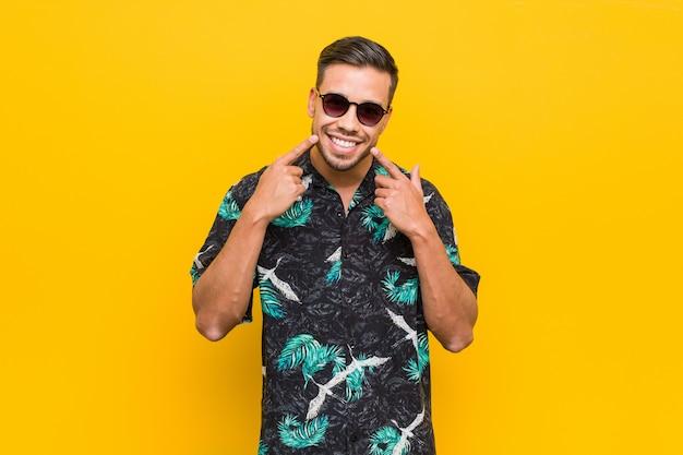 Jeune homme philippin portant des vêtements d'été sourit, pointe ses doigts vers la bouche.