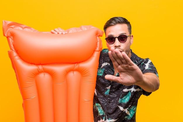 Jeune homme philippin tenant un lit gonflable