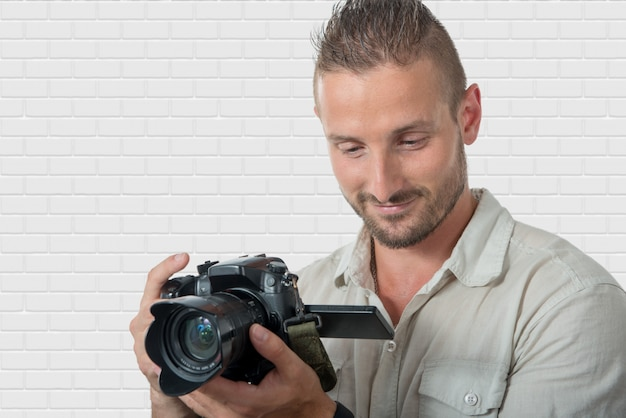 Jeune homme photographe avec appareil photo reflex numérique