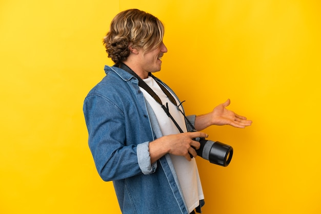 Jeune homme photographe isolé sur fond jaune avec une expression de surprise tout en regardant de côté