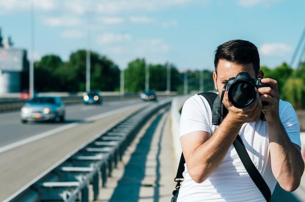 Jeune homme photographe prend des images avec l'appareil photo reflex numérique en plein air