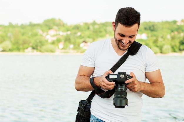 Jeune homme photographe prend des photos avec l'appareil photo reflex numérique