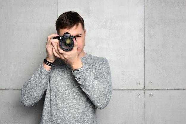 Jeune homme photographe regardant dans le viseur d'un appareil photo numérique